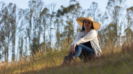 Portrait of beautiful long-haired hispanic young woman with a hat very cheerful sitting in a field against a background of unfocused green trees during sunset