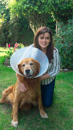 Beautiful Hispanic young woman hugging her injured Golden Retriever dog with a plastic cone on her neck in her home garden during sunset
