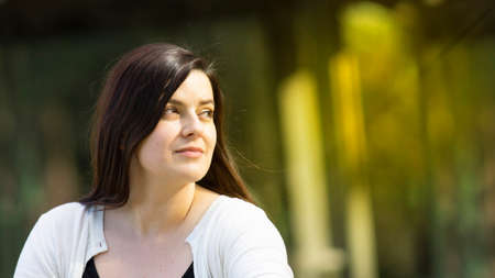 Portrait of beautiful Hispanic young woman with long hair looking to the right against a background of unfocused trees during sunset with copy space
