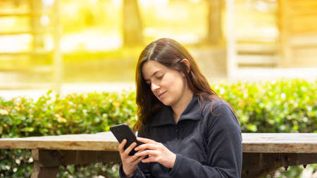 Beautiful Hispanic young woman reading a message on her cell phone sitting on a park bench during the morning