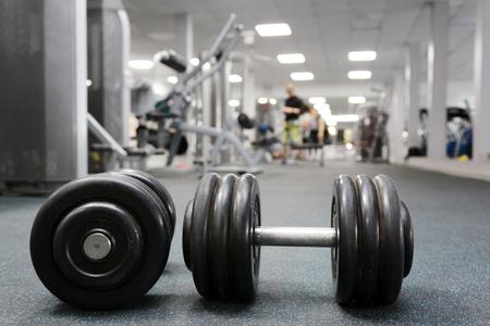 Hantle na podłodze w siłowni