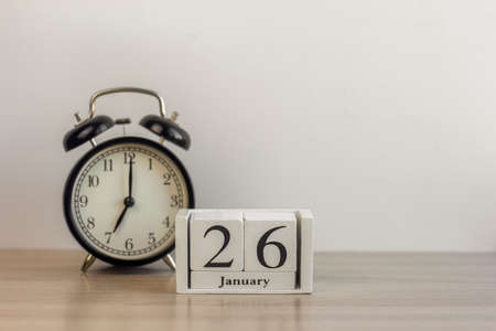 January 26 on a white calendar, next to a retro alarm clock on a light background. Calendar for January. Copy of the space.
