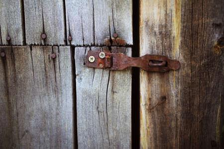 Old rusty lock hanging on the gray wooden door. Door rusty loop