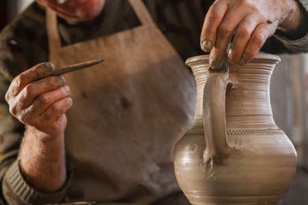 Potter working a piece of clay. Makes a jug