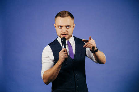 the showman: The entertainer. Young elegant talking man holding microphone, Isolated on blue background Stock Photo