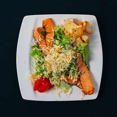 jorobado: Grilled salmon with spinach and seasonal vegetables salad - healthy dinner idea. on white plate, black background Foto de archivo