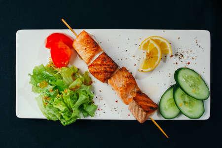 Shashlik de salmón con verduras en el plato blanco y fondo negro.