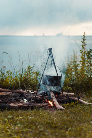 Travel a kettle over a fire burning on the river and sunset backgroun.Cooking over a campfire