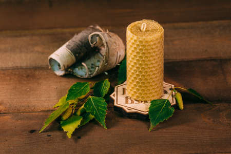 Wax candle with birch bark and leaves. Wooden background, home atmosphere. Stock Photo