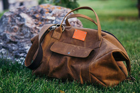 Retro brown shoes and man leather bag in bright colorful summer grass in the park