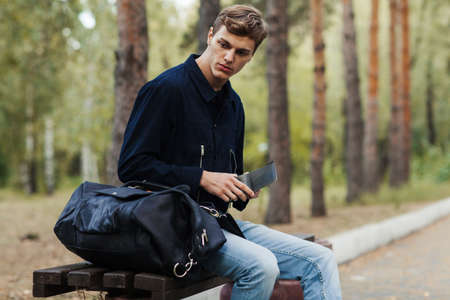 euromoney: The young man sits on a shop and looks in the purse. Stock Photo