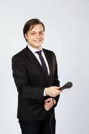 The interviewer. Young elegant man holding microphone Imagens