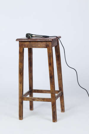 This is a photo of a microphone sitting on top of a wooden stool lite from above. Shot on a white background