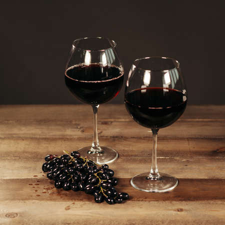 Two glasses of red wine and fresh grapes on dark wooden background Stock Photo