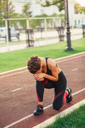 Athletic woman on running track touching hurt leg with knee injury during workout. Park in the background.