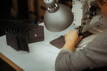 Making leather wallets on a sewing machine by a craftsman on a white table. Nearby are several ready-made leather wallets. On the table is a lamp and a sewing machine. Фото со стока