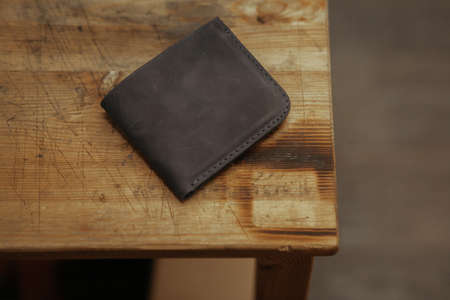 Black leather wallet on wooden background. Top view. Handmade leather wallet Фото со стока