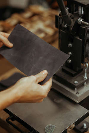 Man holding leather craft and working. Press machine in the workshop for doing the embossed logo and letters on the leather product that heats the cliche and squeezes the desired image on the material