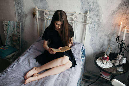 A girl is reading a book on a bed in a romantic black dress. Stockfoto
