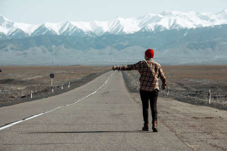 Man in red hat walking down a mountain road