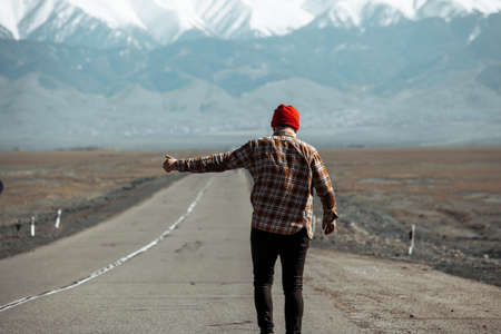 Boy hitchhiking in the middle of open road