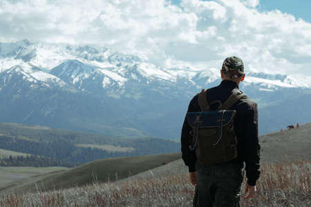 Man in cap with backpack standing in front of mountains Reklamní fotografie