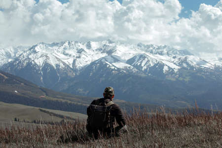 Man in camouflage sitting in dead grass in front of mountains