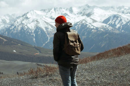 Guy in red beanie standing in front of mountains Stock Photo