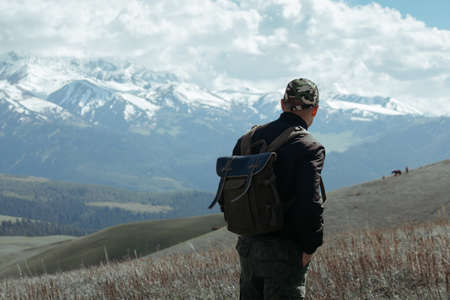 Man in cap and jacket looking at the cloudy sky and mountains