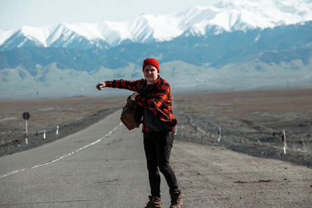 Hipster in red hitchhiking on old dusty road