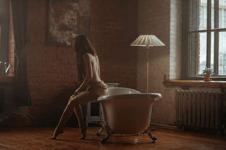 Girl sitting on white bath in old decorated room Banco de Imagens