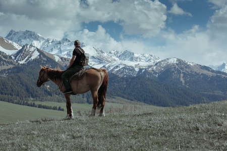 Man on the horse looking at the mountains
