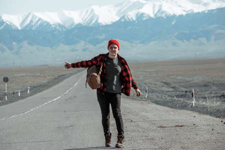 Man in shirt and backpack hitchhiking down on dusty road