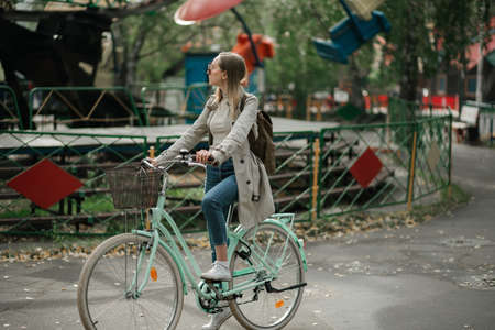 Young girl ridding on bicycle through amusement park