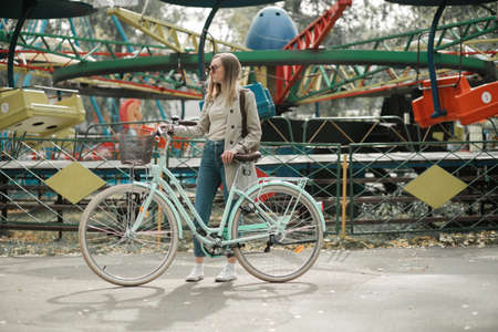 Girl looking away in amusement park with bike
