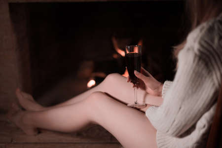 Attractive blond young woman in white sweater warming by the fireplace at home