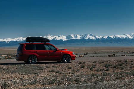Car standing on road with mountains with snow peaks at the background