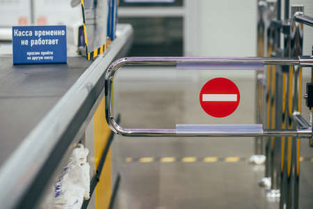 The closed Barrier with the sign in a supermarket. Text on the plate: The cash register is temporarily closed.