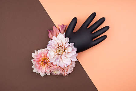Black rubber glove decorated with fresh flowers. Fall aesthetic in pastel palette. Contrast brown and pastel peach background with abstract details. Pandemic medical rubber glove protects nature. Stock Photo