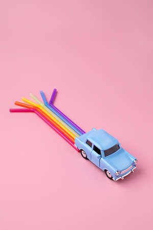 Blue car toy with rainbow trail make from straws. Minimal pop art travel concept. Flat lay. Banque d'images