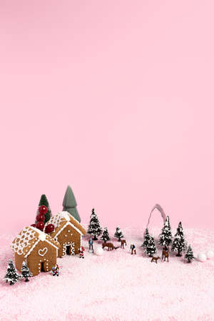 Creative Christmas scene made with with ginger houses, Santa Claus, trees, snow and reindeers on pink pastel color background. Minimal New Year concept.