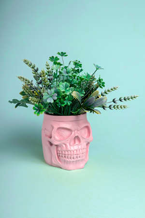 Pink skull with leaves on pastel background. Halloween creative concept. Magic surreal image. Witch ritual atmosphere.