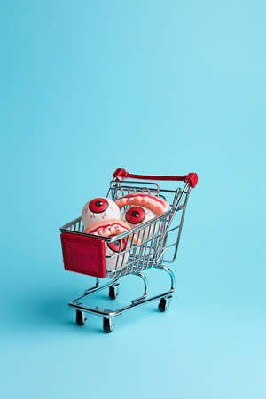 Creative layout made with eyeballs in shopping cart. Minimal Halloween shopping background. Invitation card, party, copy space. Reklamní fotografie