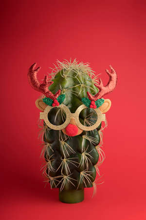 Creative Christmas layout made with cactus wearing sunglasses and antlers on a red background. Minimal New Year season concept. Celebration, greeting card, banner.