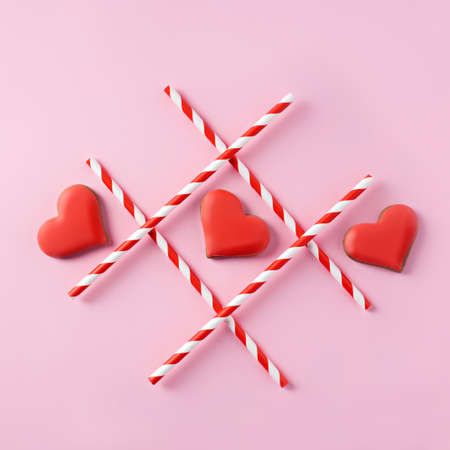 Tic-tac-toe with straws and red hearts on pink background. Love wins. Creative Valentines day or romantic concept. Flat lay, top view, copy space.