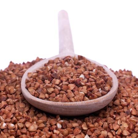 Spoon with buckwheat  lies buckwheat, shallow depth of field, isolated Stock Photo - 15005324