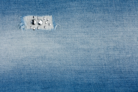 Torn light-blue jeans with rhinestones , background photo