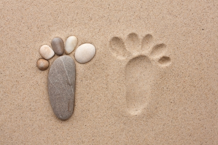 The footprint made up of stones on a sandy background photo