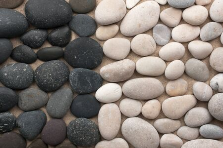 Black and white stones lie side by side on the sand