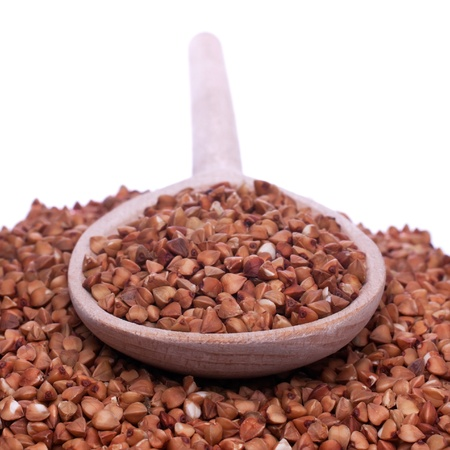 Spoon with buckwheat  lies buckwheat, shallow depth of field, isolated Stock Photo - 15465701